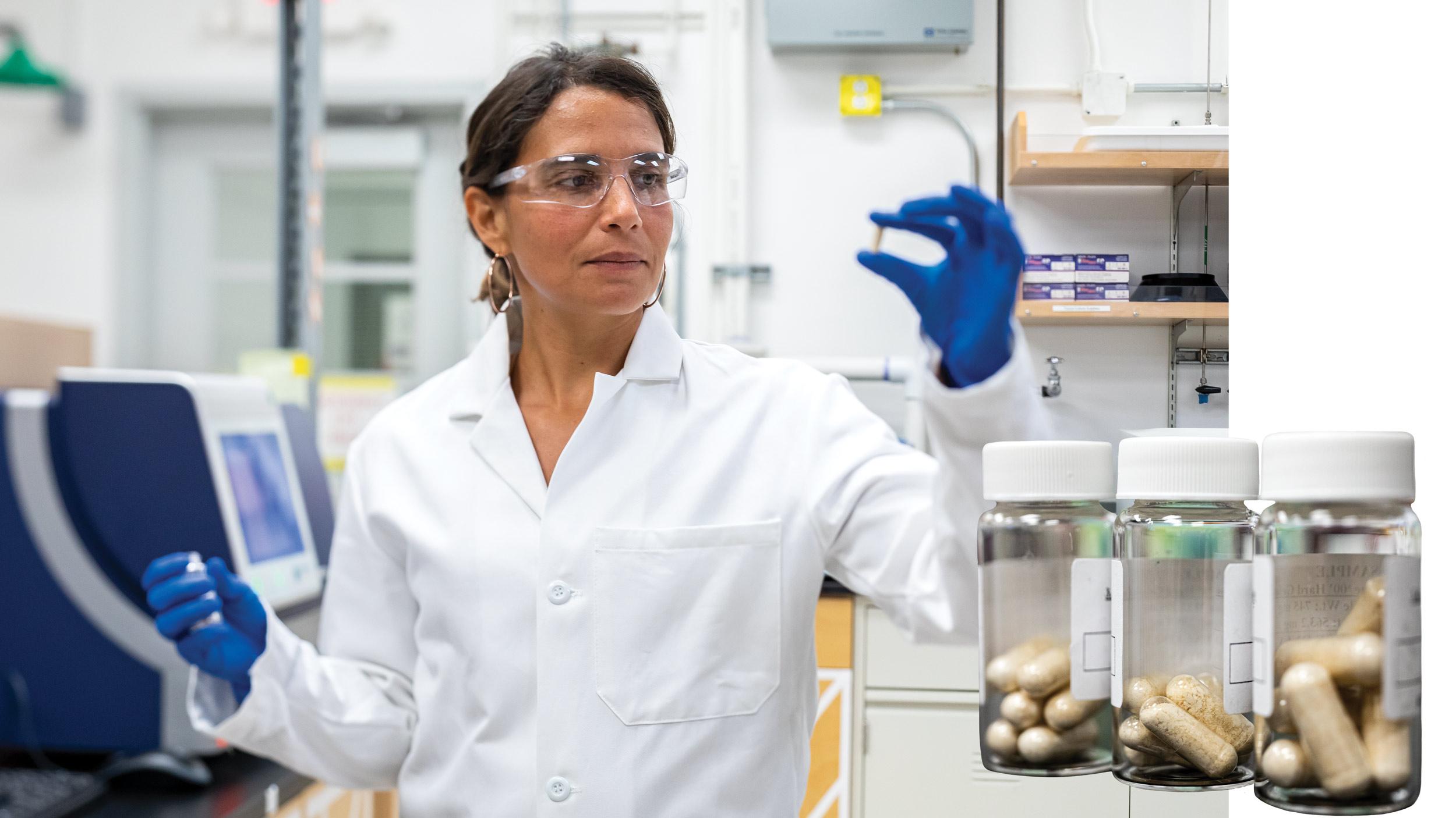 Rebecca Abergel in her lab holding a pill