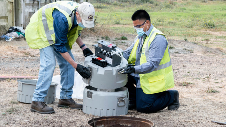 UC Berkeley workers remove a wastewater autosampler from a sewer drain