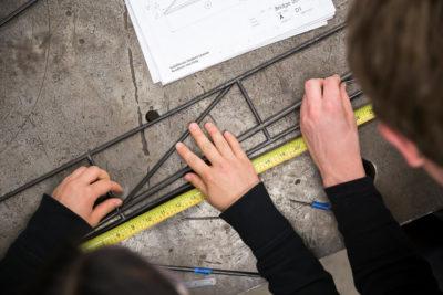 Students measuring a steel bridge component