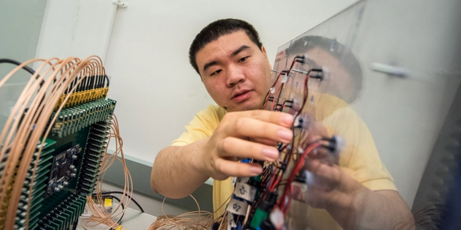 Chengzhi Shi checks the connections between the transducer array and the digital circuit.